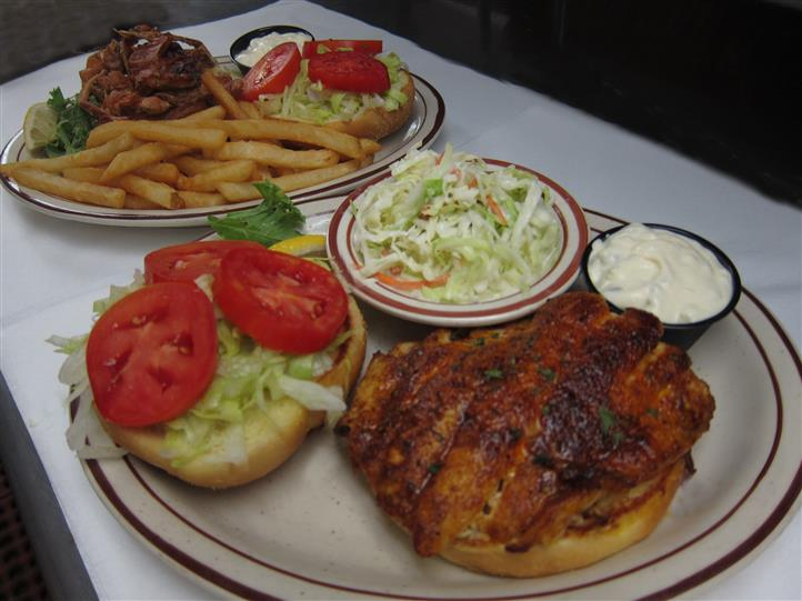 grilled chicken on a bun with coleslaw and fries