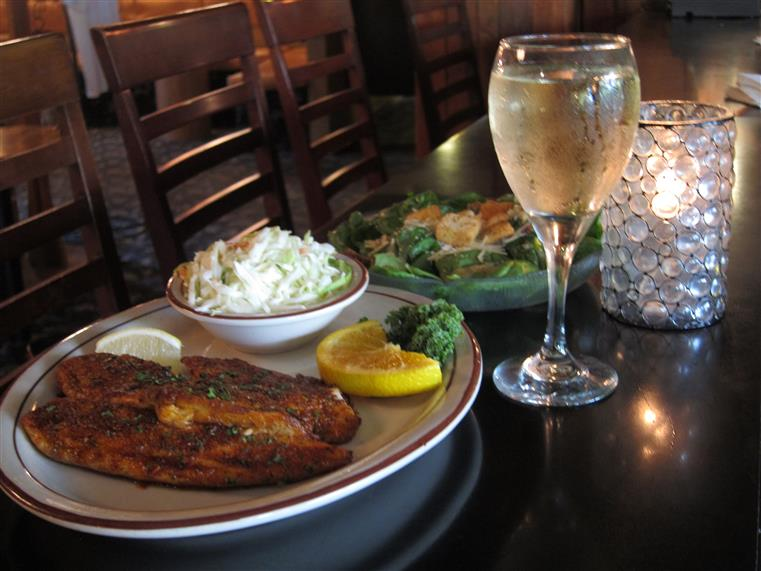 baked fish with coleslaw and a glass of wine