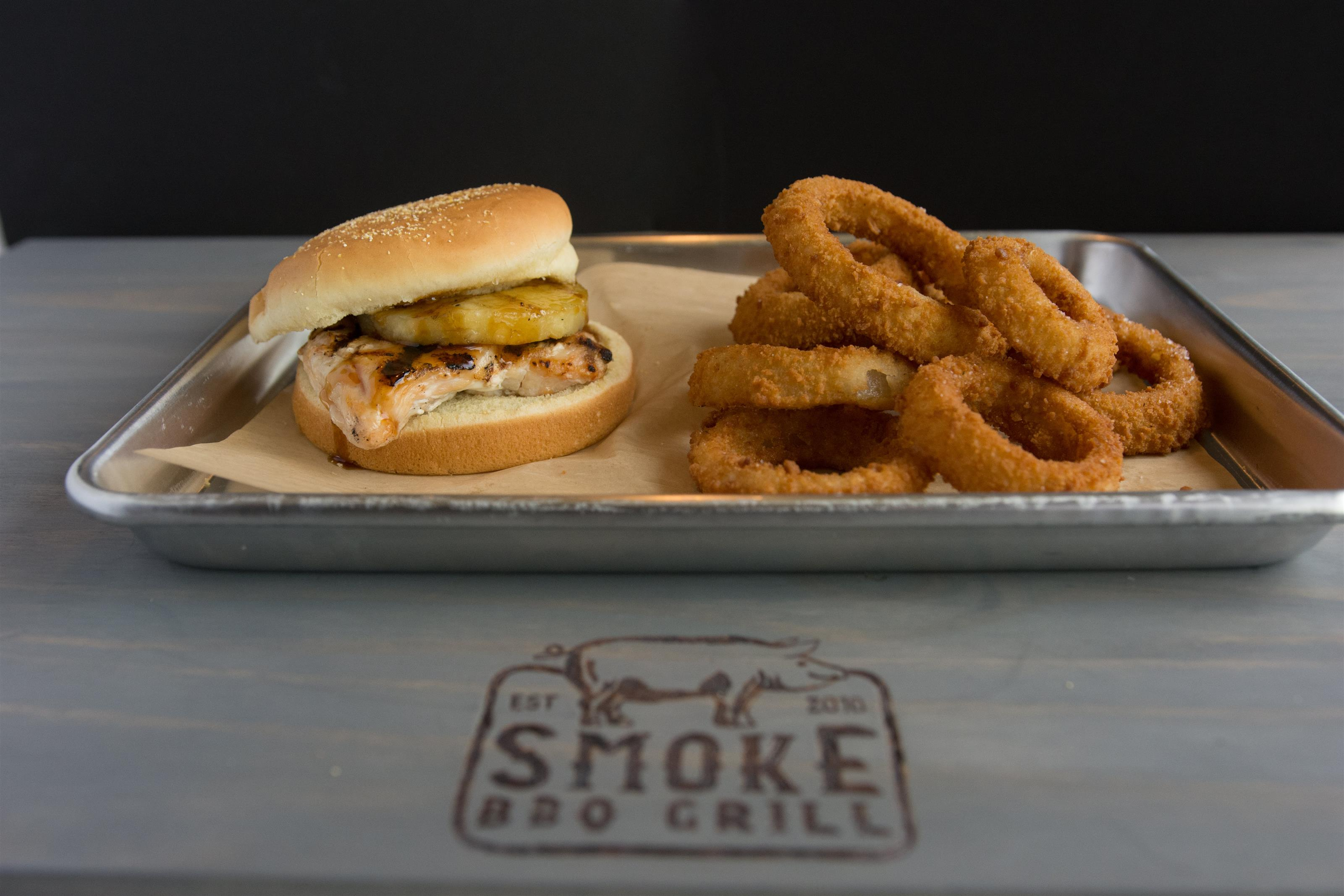 a chicken sandwich with a pickle on top with a side of onion rings