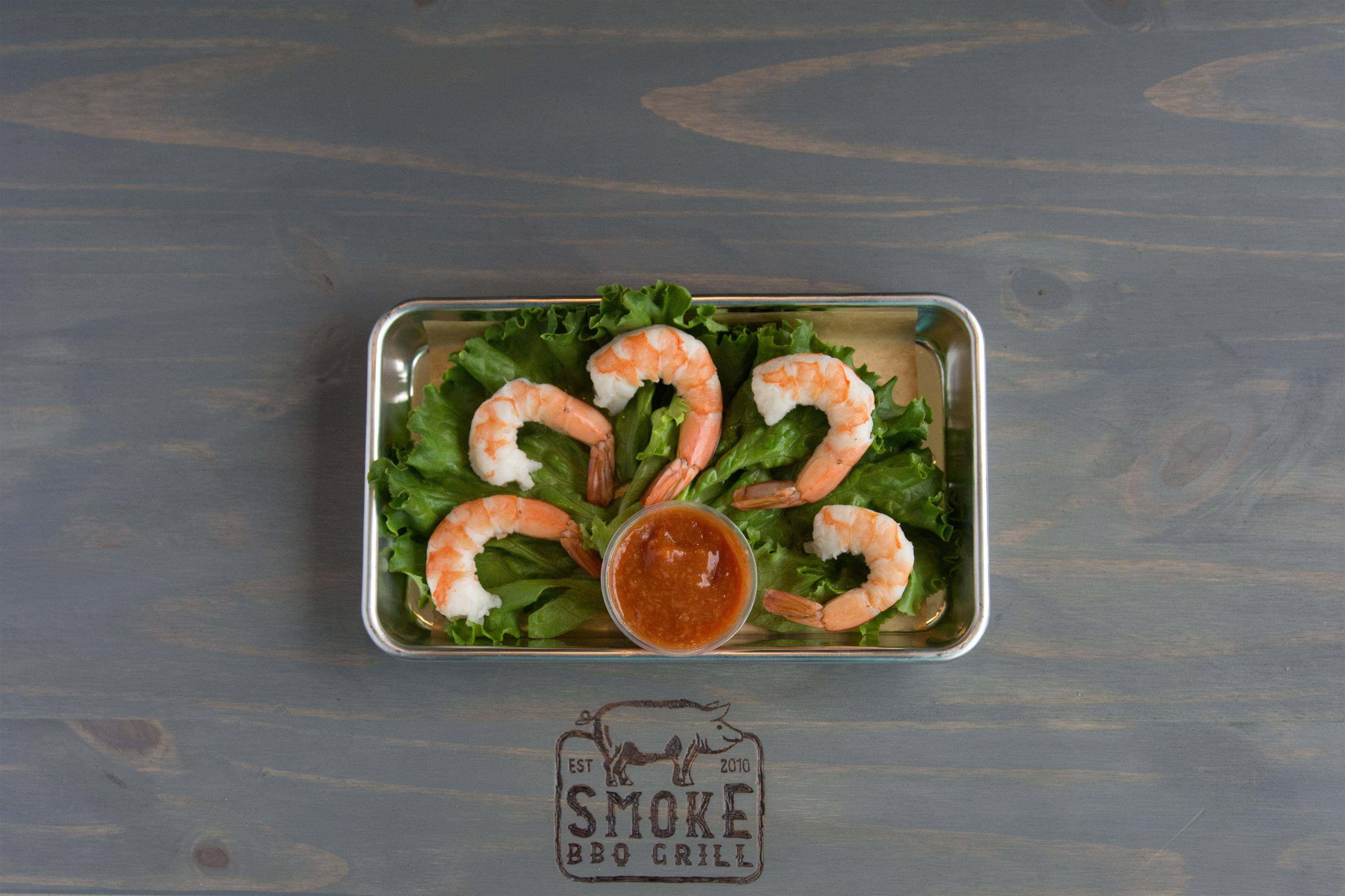 four shrimp on a bed on lettuce on a platter with a side of cocktail sauce