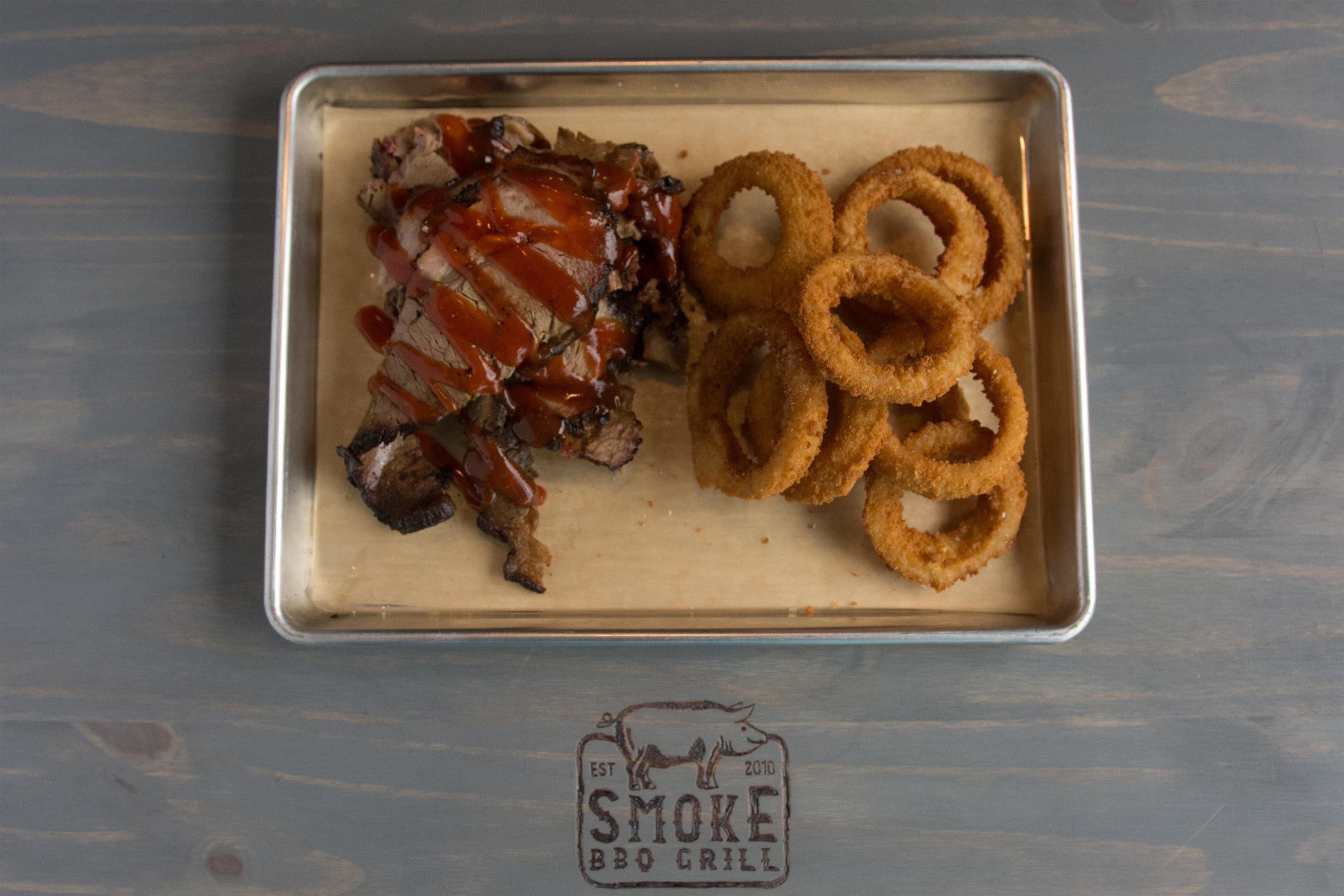 roast beef with barbecue sauce on top with side of onion rings
