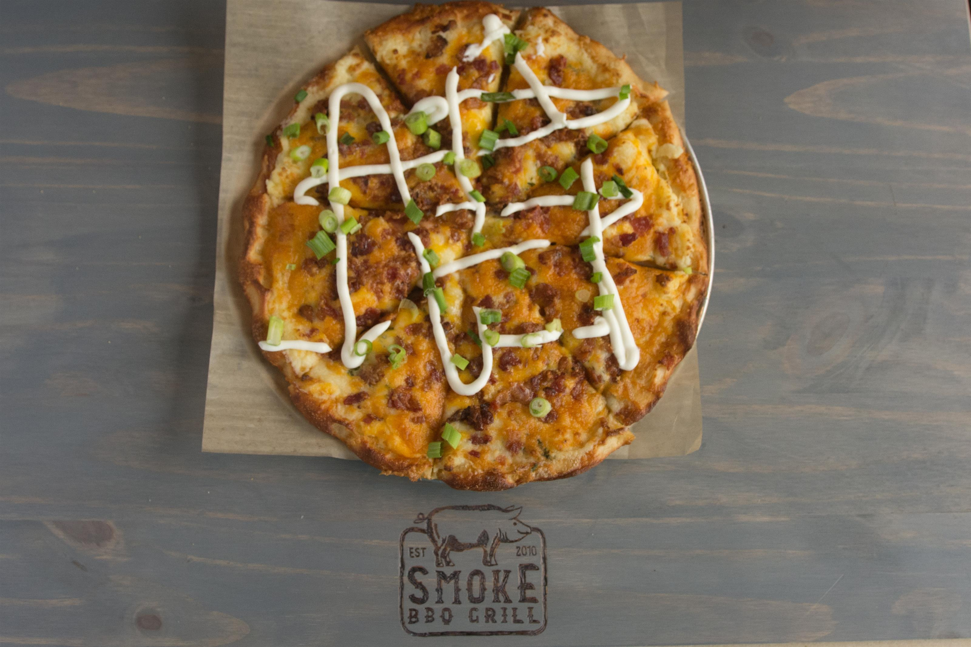 cheese pizza with bacon and scallions on top