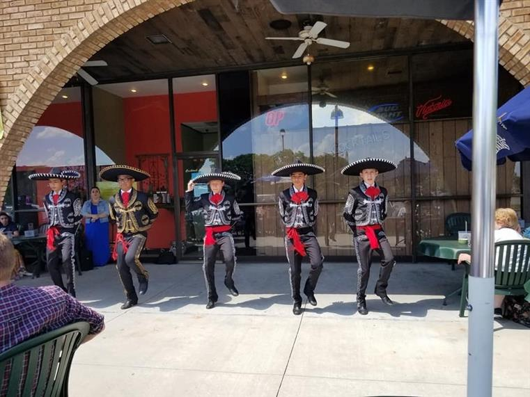 four gentlemen wearing sombreros performing a dance outside the establishment