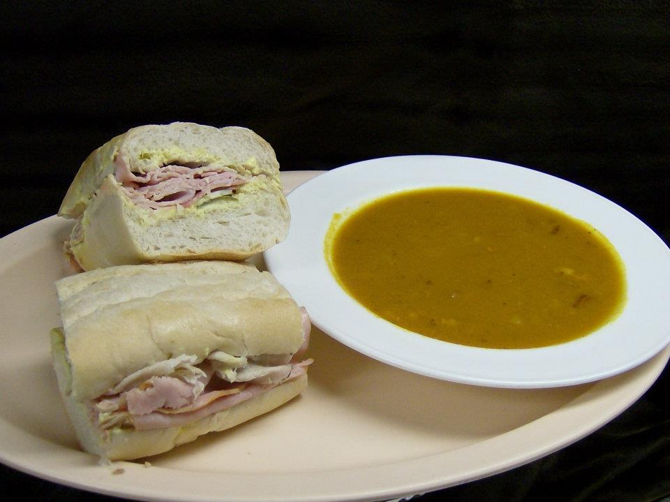 ham and cheese sandwich on french bread with a bowl of soup