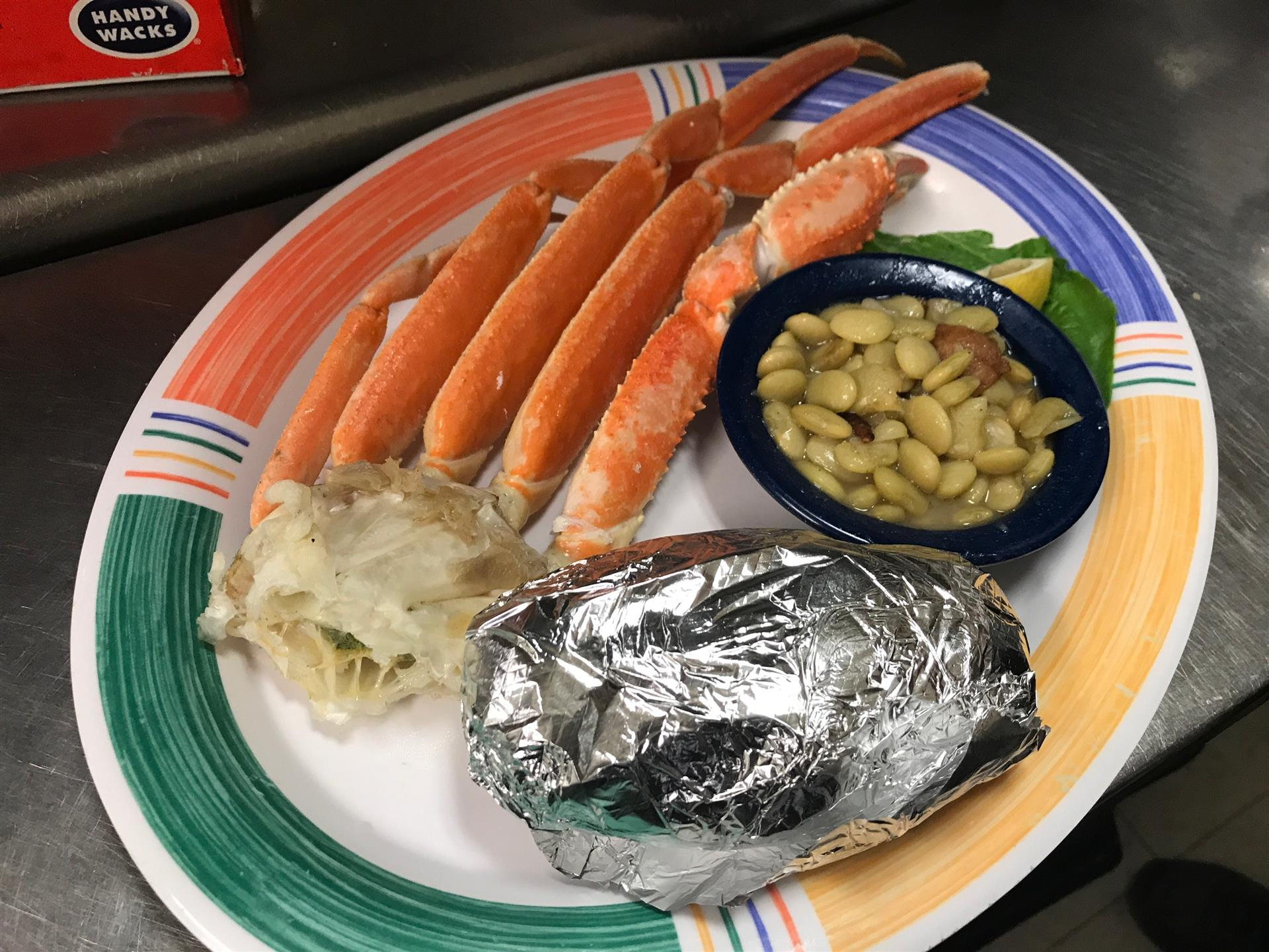 crab legs with a side of corn and a baked potato