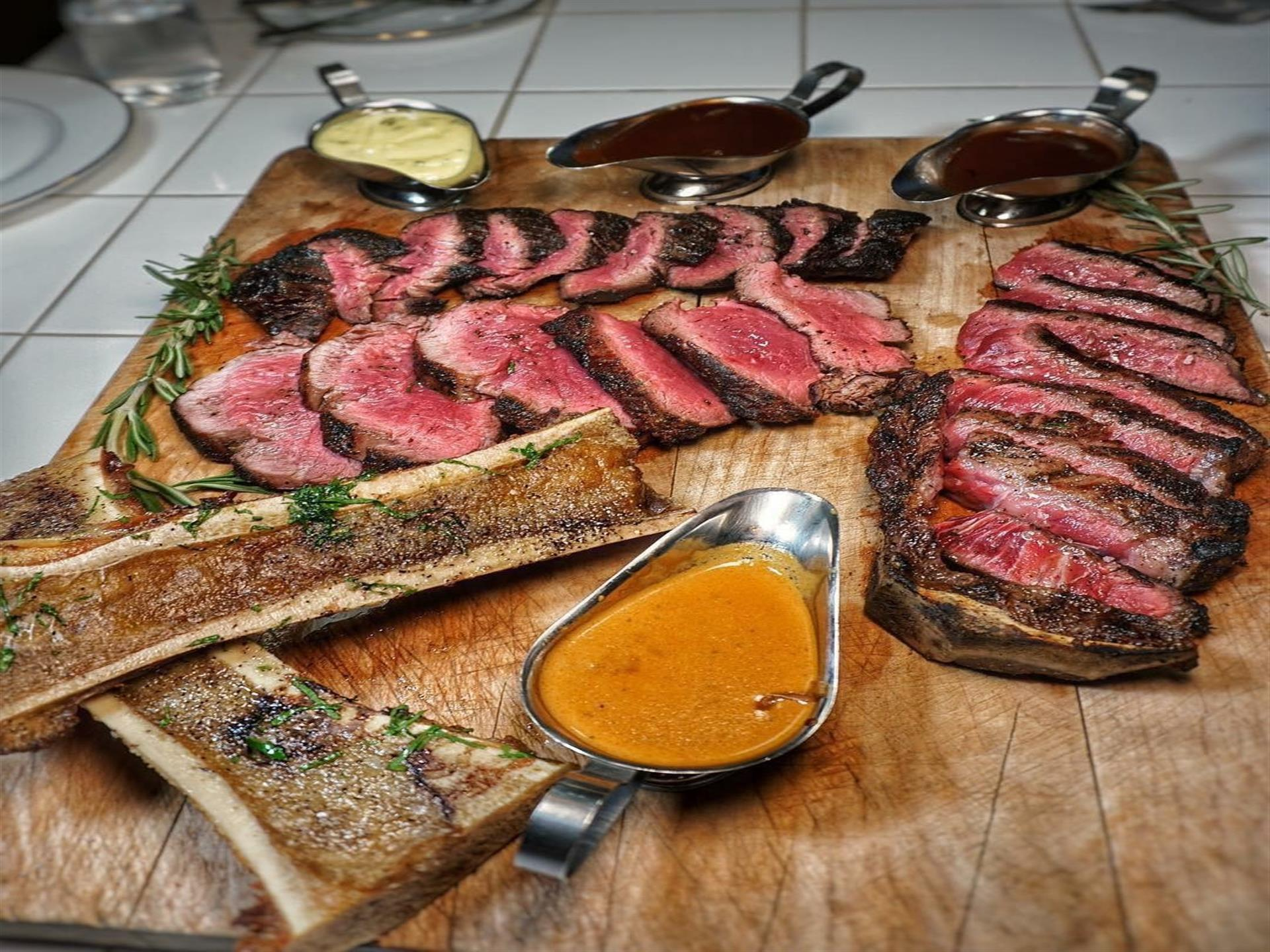 slices steak with sauces on a cutting board