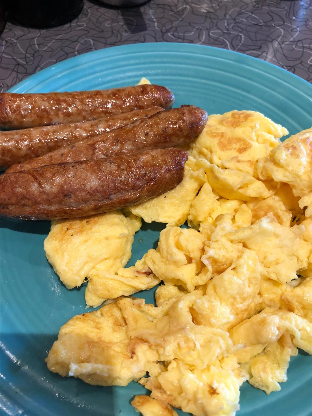 a blue plate with scrambled eggs and three breakfast sausages on it