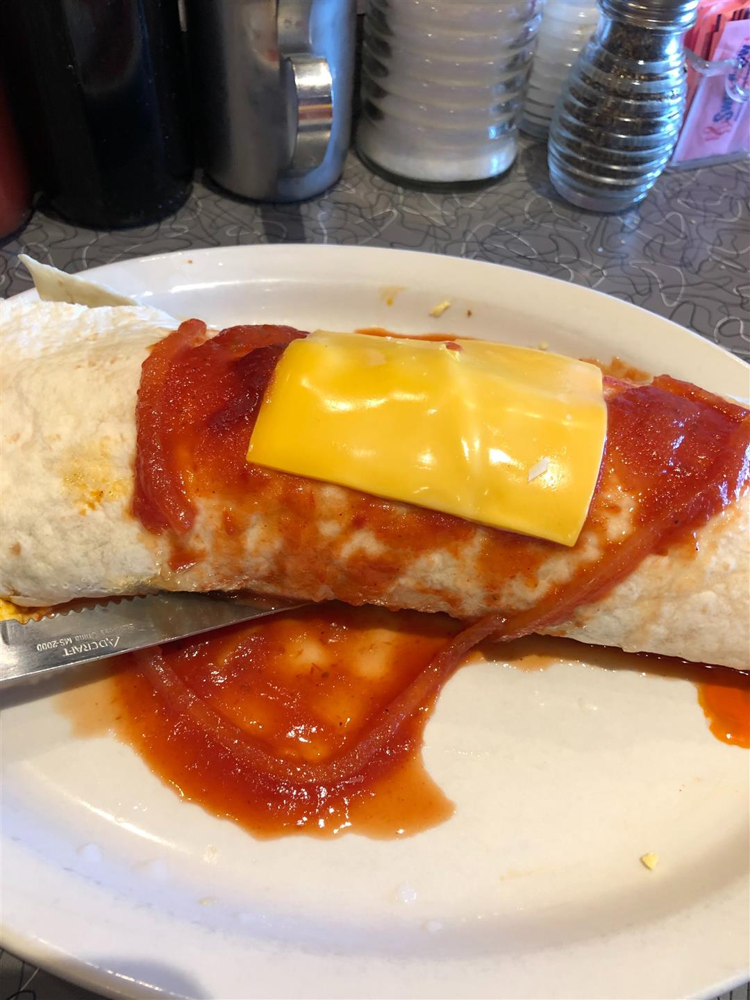 a breakfast burrito covered in red sauce and an american cheese slice on a plate