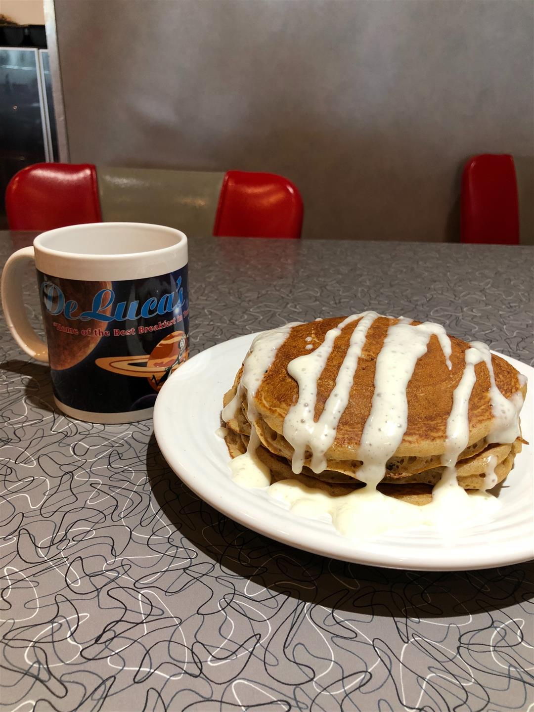 two buttermilk pancakes on a plate drizzled in gravy with a coffee mug next to it