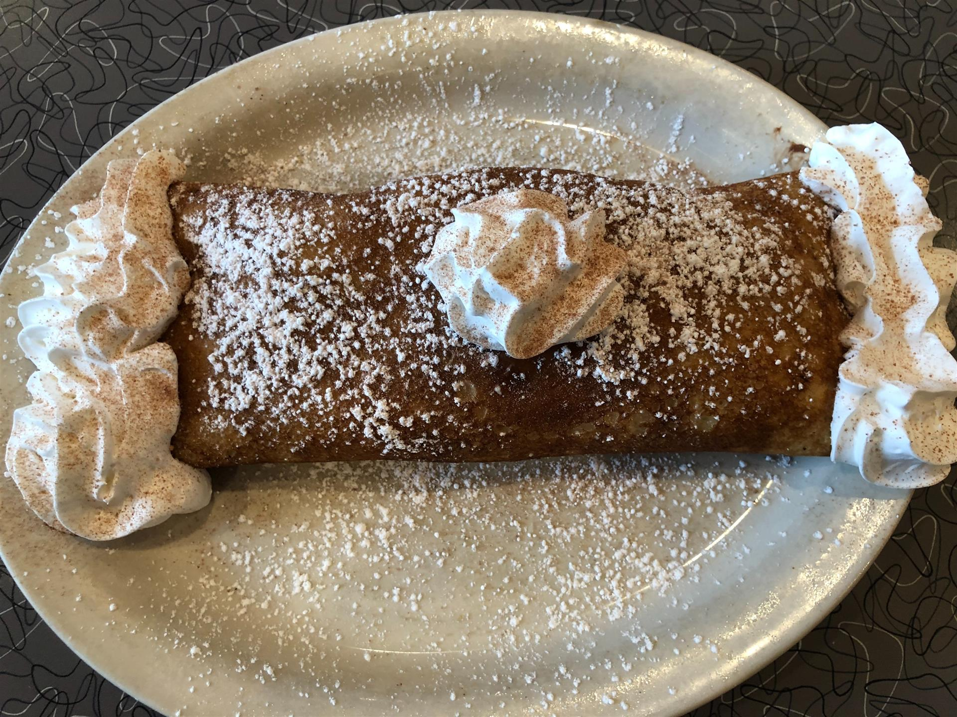 a breakfast crepe covered in whipped cream and powdered sugar