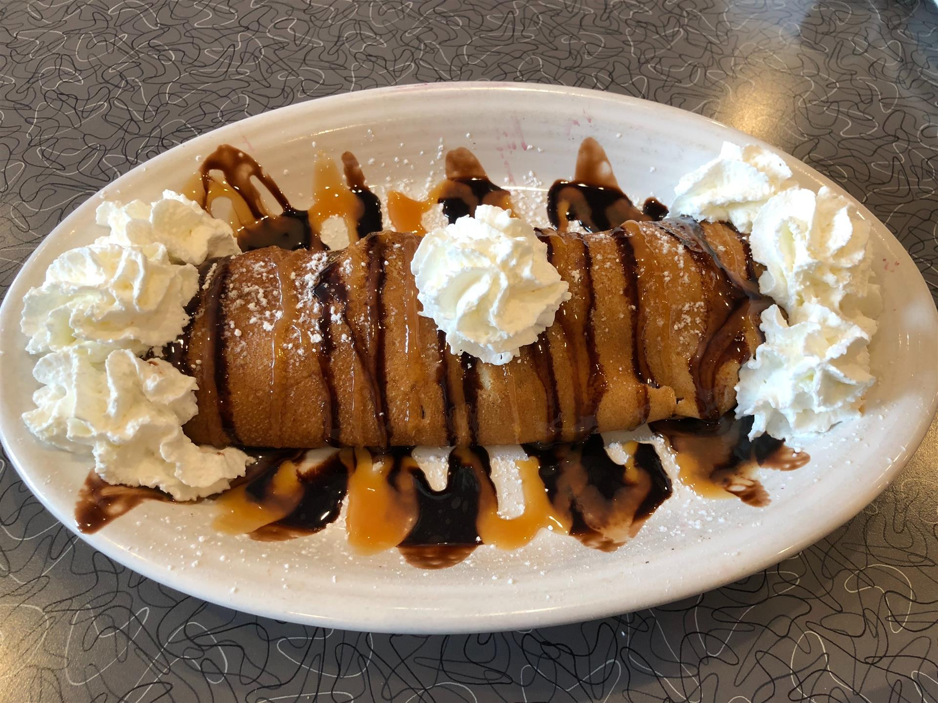 a breakfast crepe covered in whipped cream, and drizzled with chocolate syrup and caramel