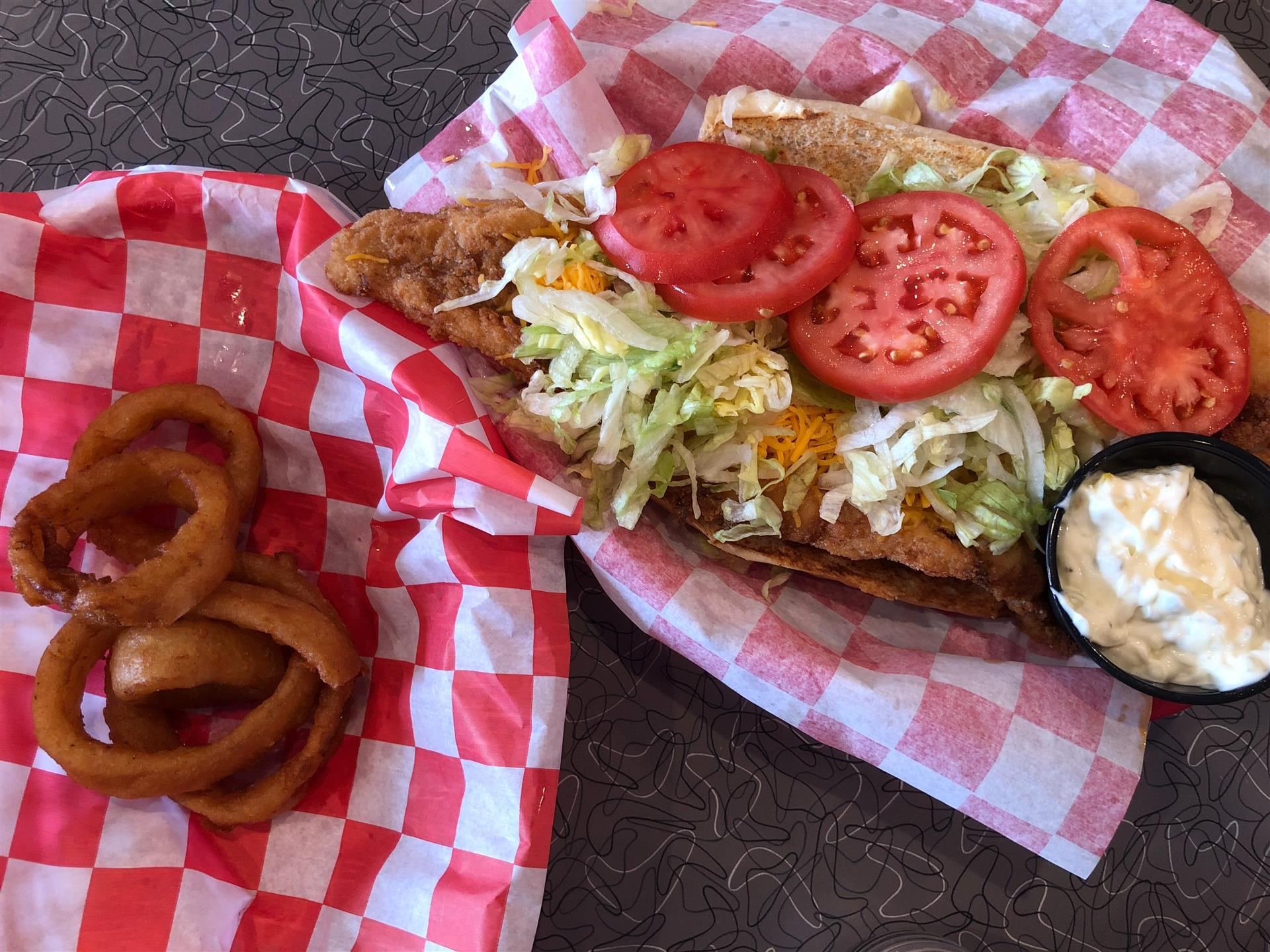 open faced chicken sandwich with cheese, lettuce, tomato and a side of dipping sauce with a side of onion rings