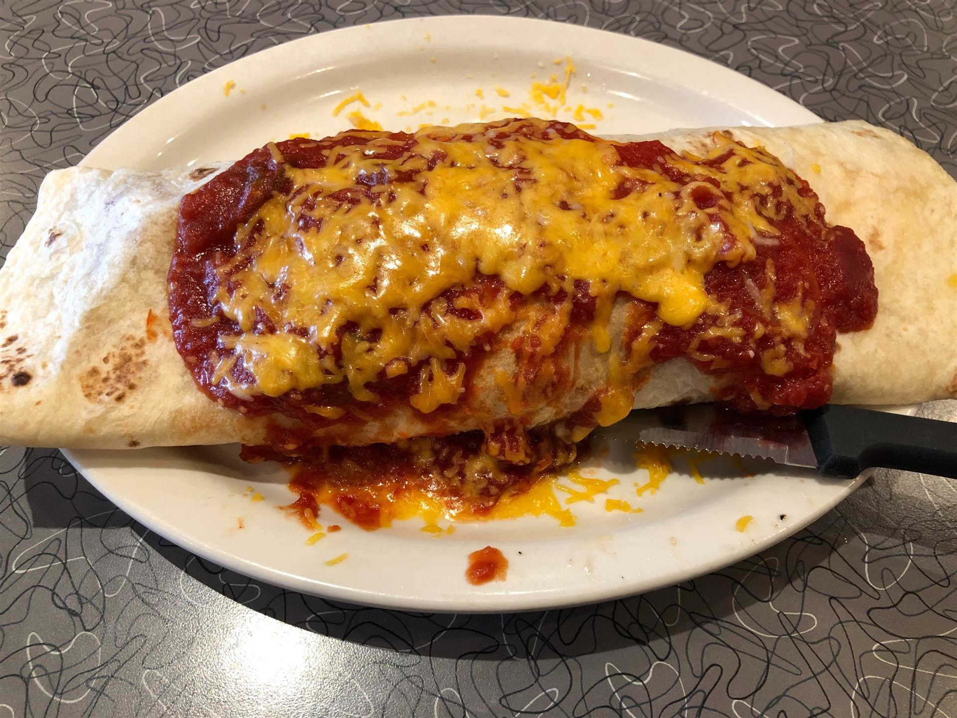 a breakfast burrito covered in red sauce and cheese