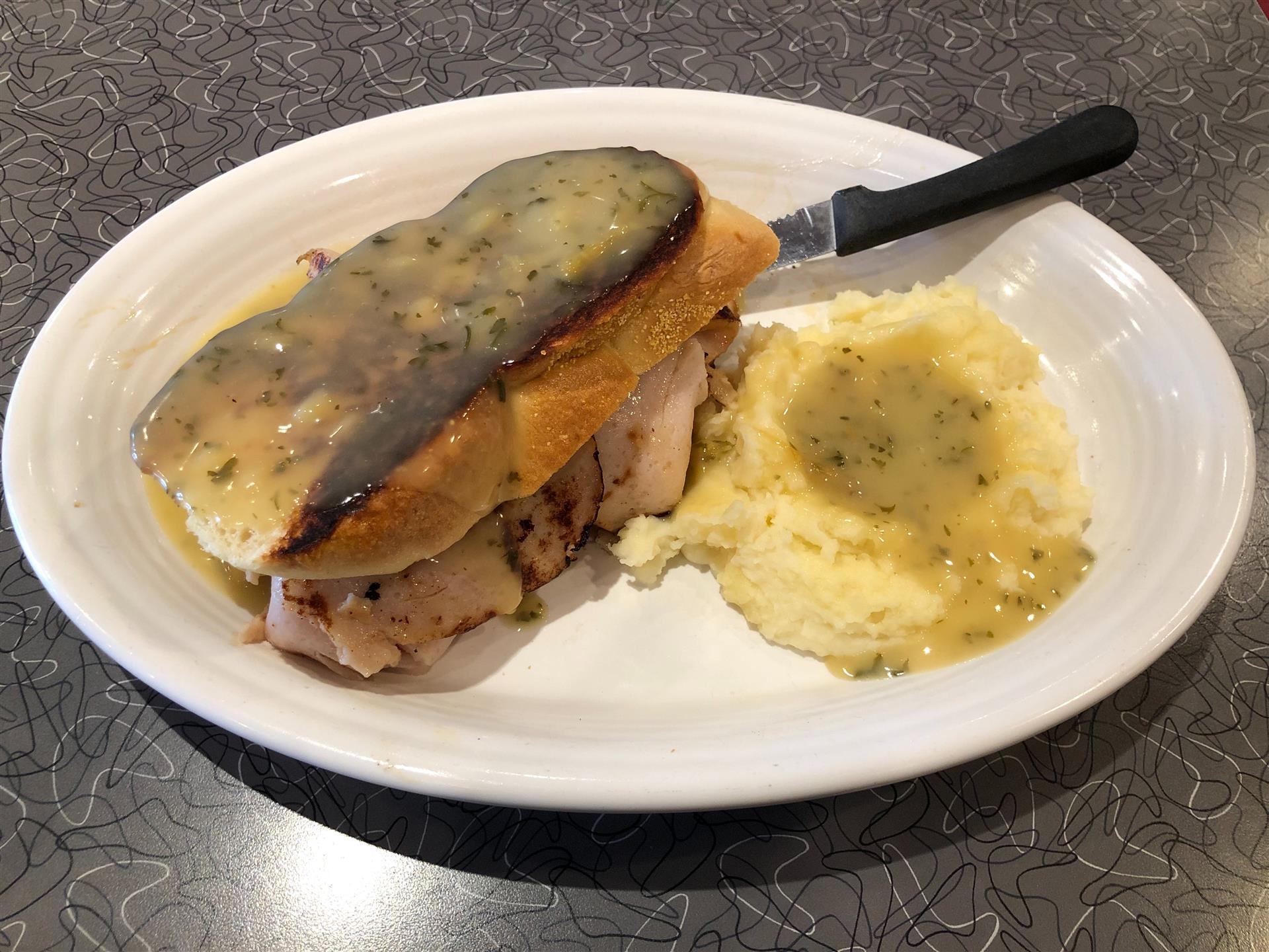 a turkey sandwich with a side of mashed potatoes both covered in gravy