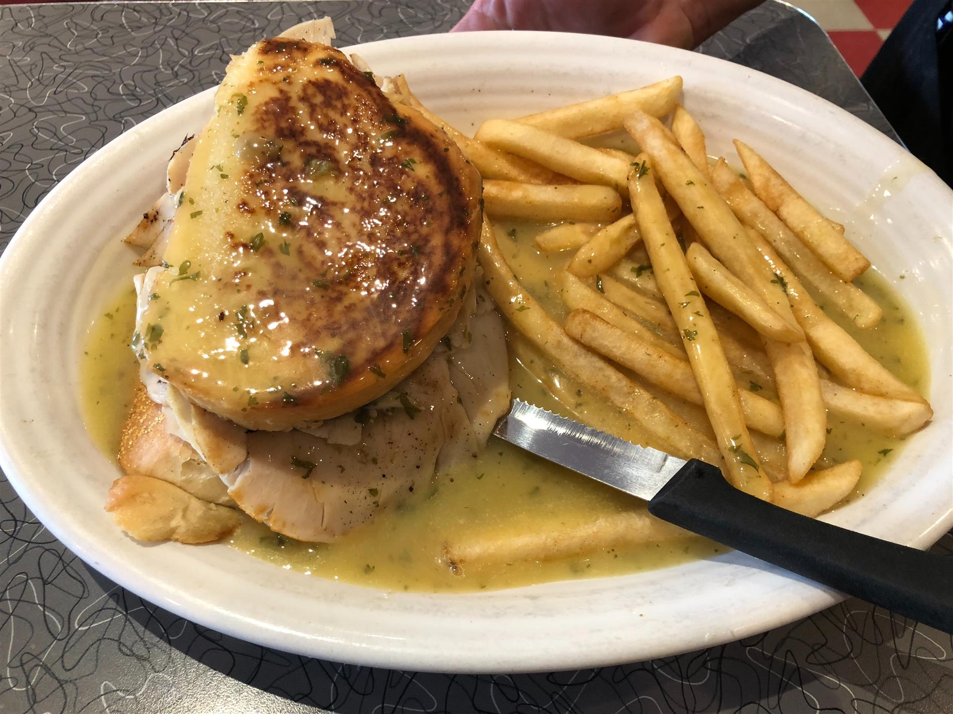 chicken sandwich on a plate with a side of fries covered in gravy