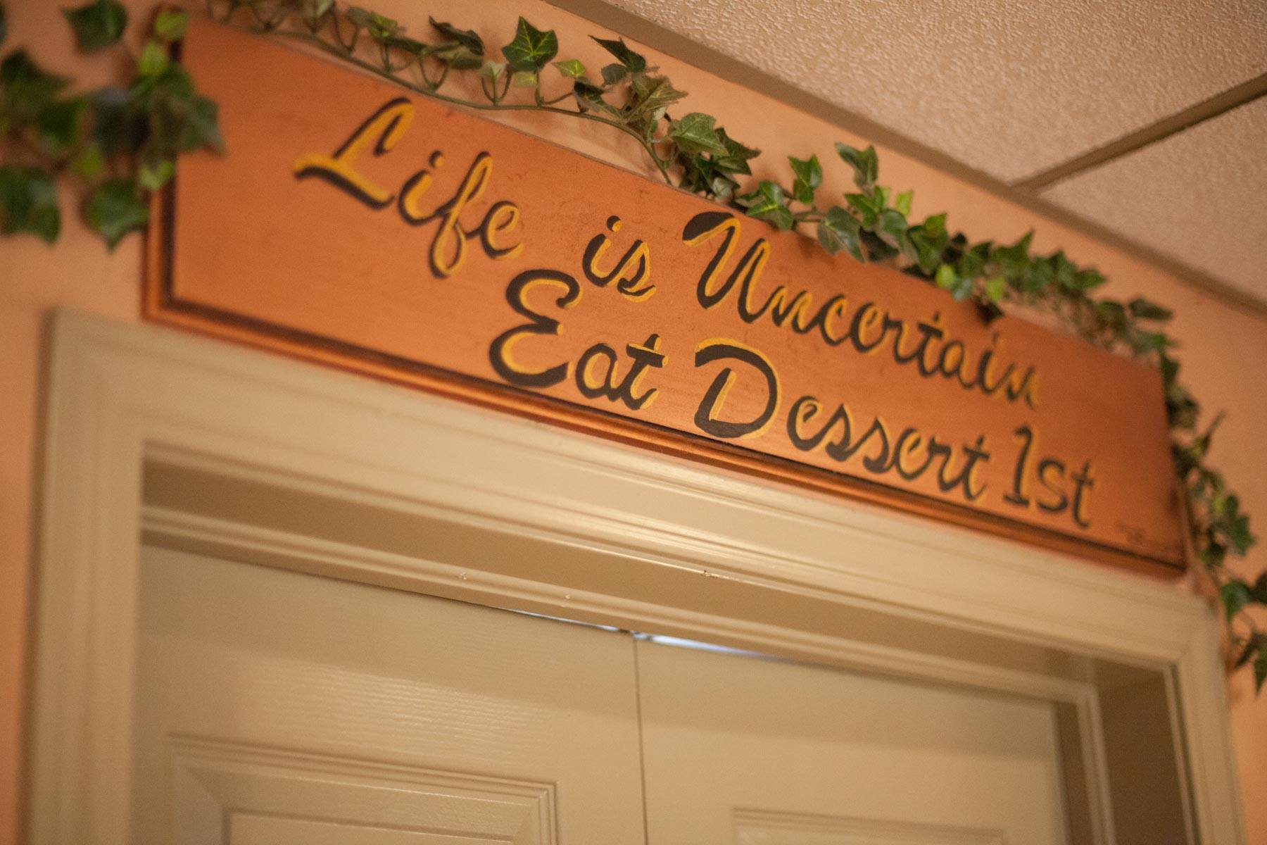 sign that reads life is uncertain eat dessert 1st