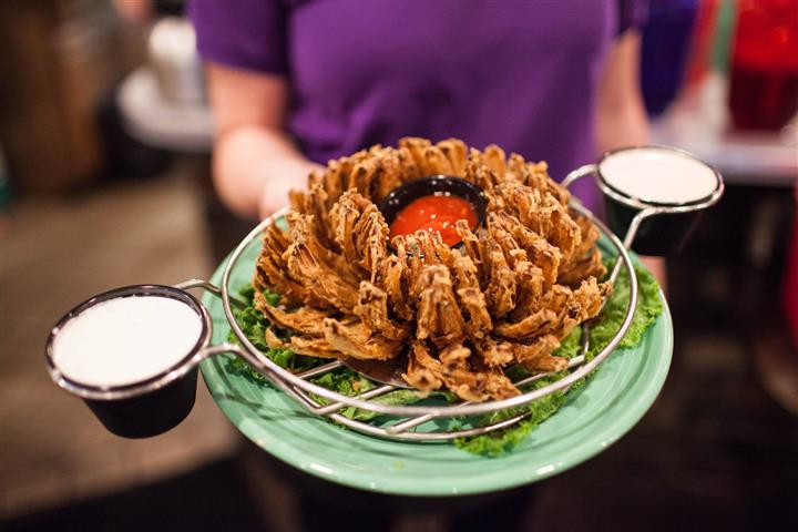 blooming onion being held by one of the waiters