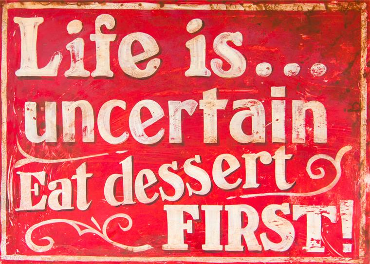 Writing on sign: Life is uncertain. Eat dessert first!