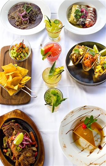 various mexican dishes being displayed in plates and bowls