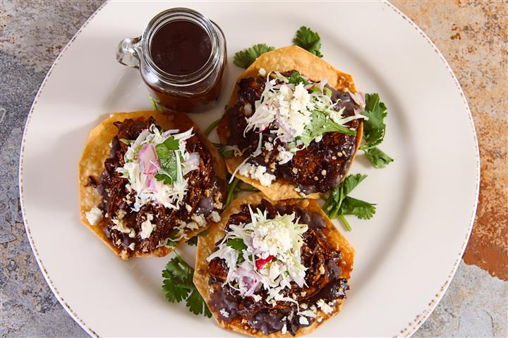 three tacos with meat and coleslaw with sauce