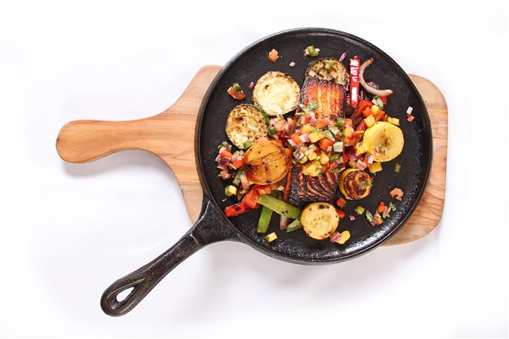 skillet with cooked fish and vegetables