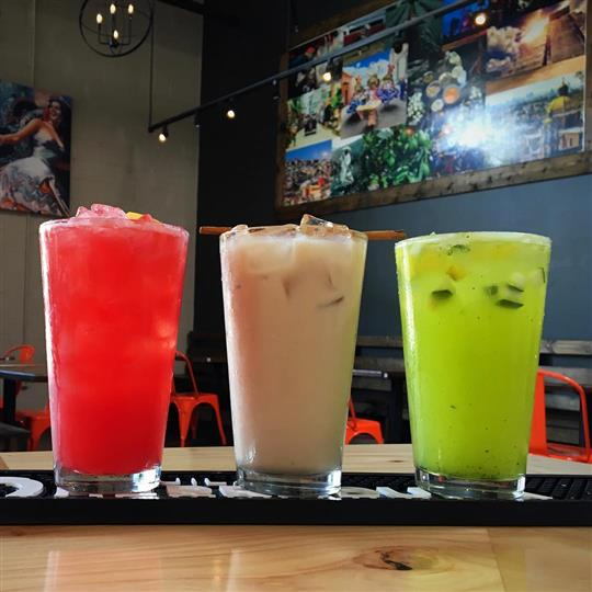 three mixed cocktails being displayed at the bar