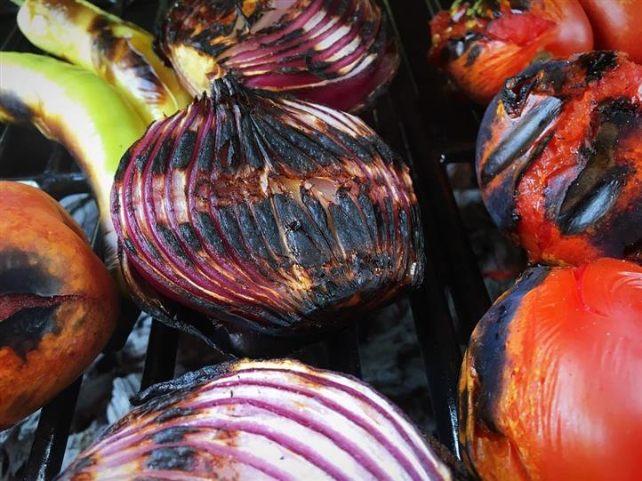 Charred onions and tomatoes on a grill
