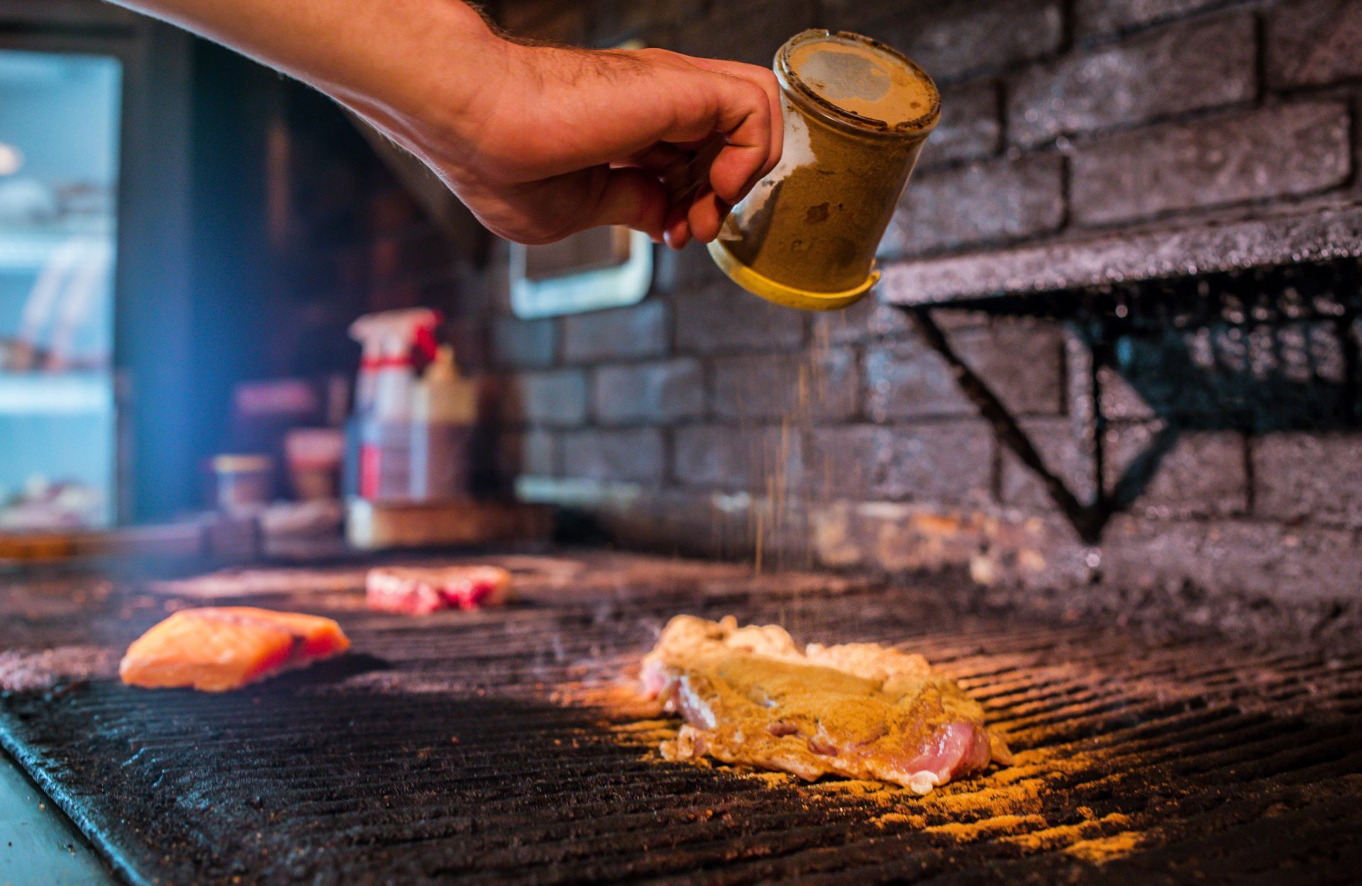 Spices being poured over a steak on a grill-top