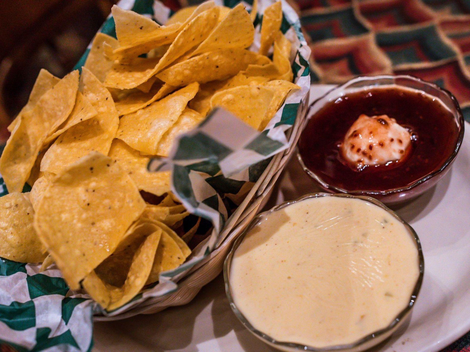 Basket of tortilla chips with cheese sauce and salsa