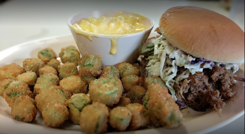 pulled pork sandwich with coleslaw on top and a side of mac and cheese and jalapeno poppers
