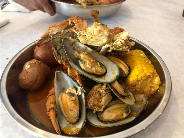 mussels, crab legs, potatoes and corn in a bowl
