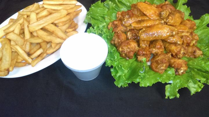 basket filled with buffalo wings and bleu cheese with a side of fries