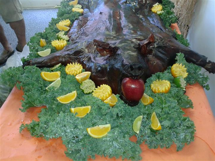 cooked fish with apple in its mouth being displaye dover  abed of lettuce