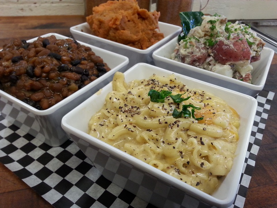 four side dishes in bowls filled with mach and cheese, mashed potatoes, beans and mashed sweet potatoes