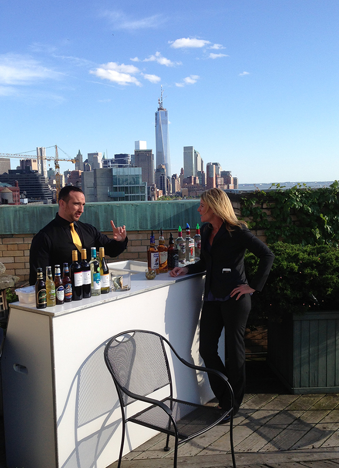 two employees standing by a bar on a rooftop