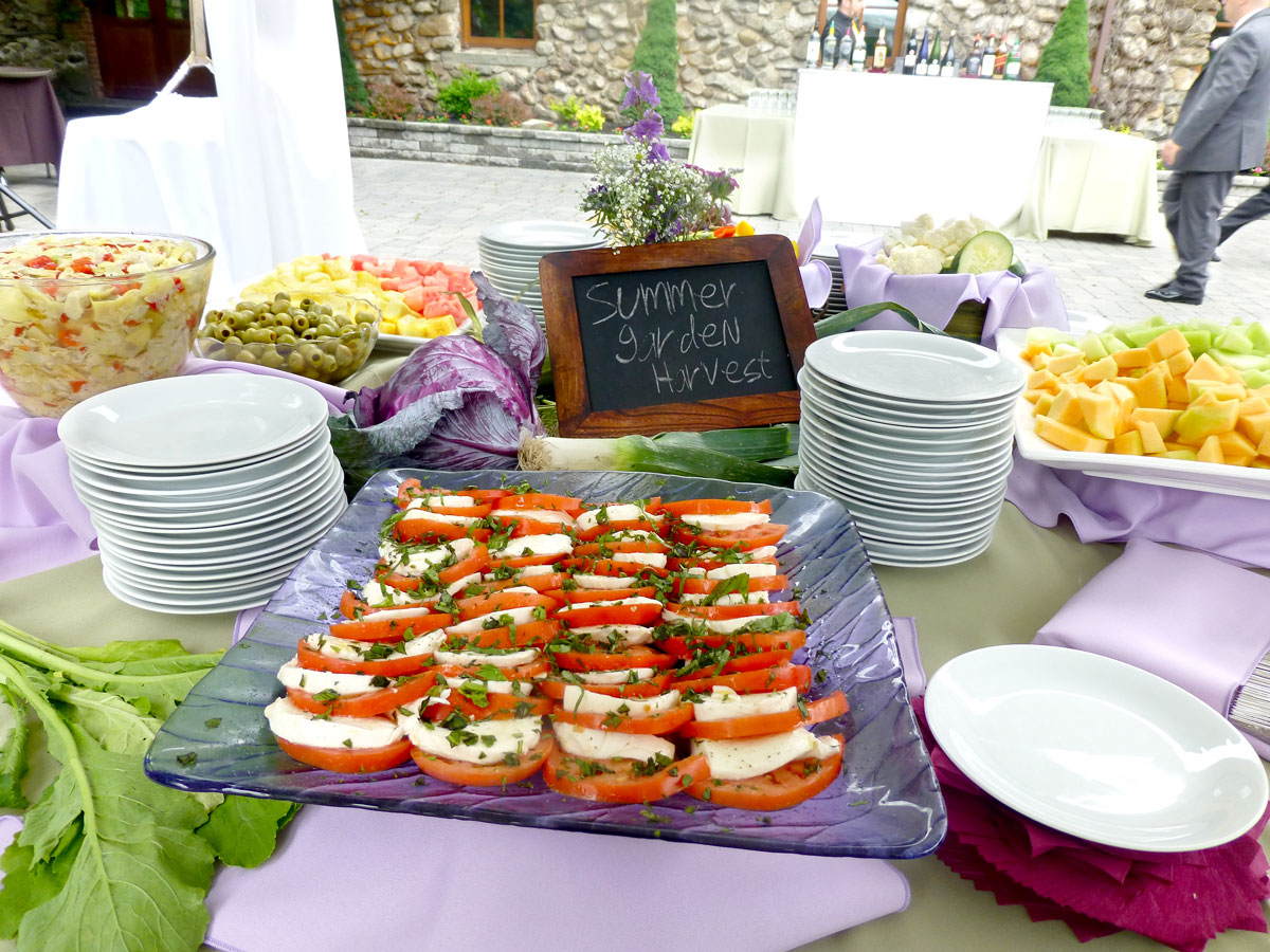 tomato and mozzarella on a platter with small plates and a sign that reads summer garden harvest