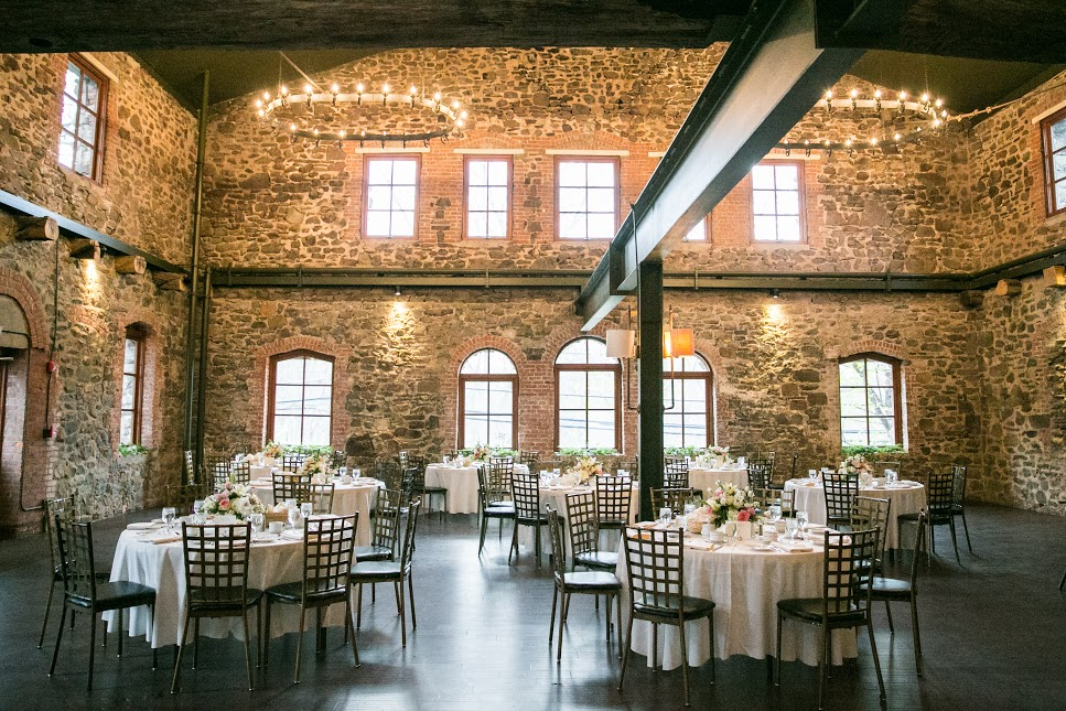 banquet tables set inside of a tall stone walled room