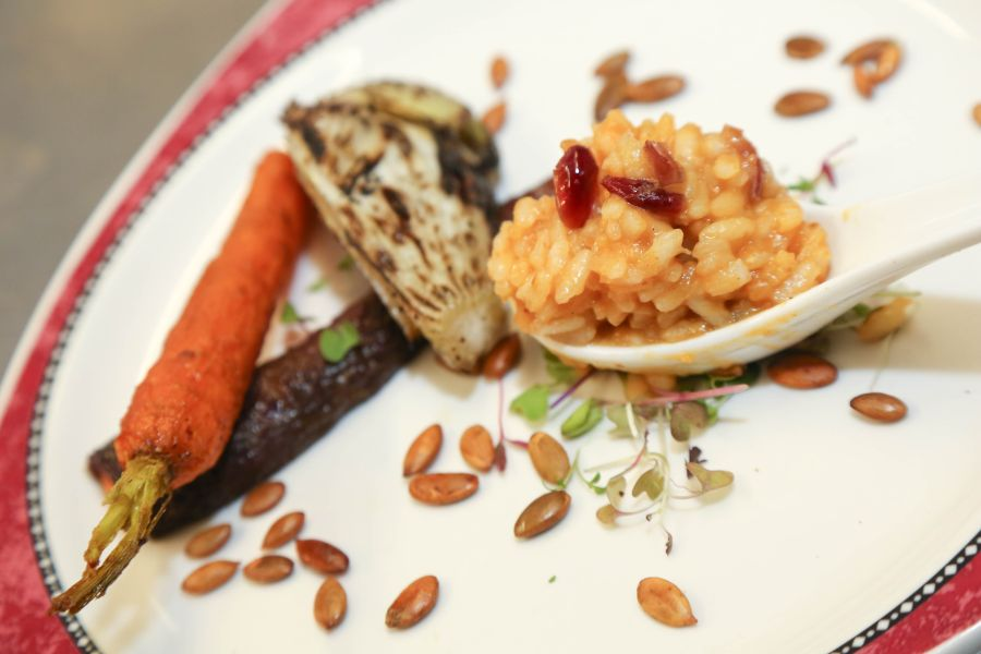risotto and root vegetables on a plate with sunflower seeds