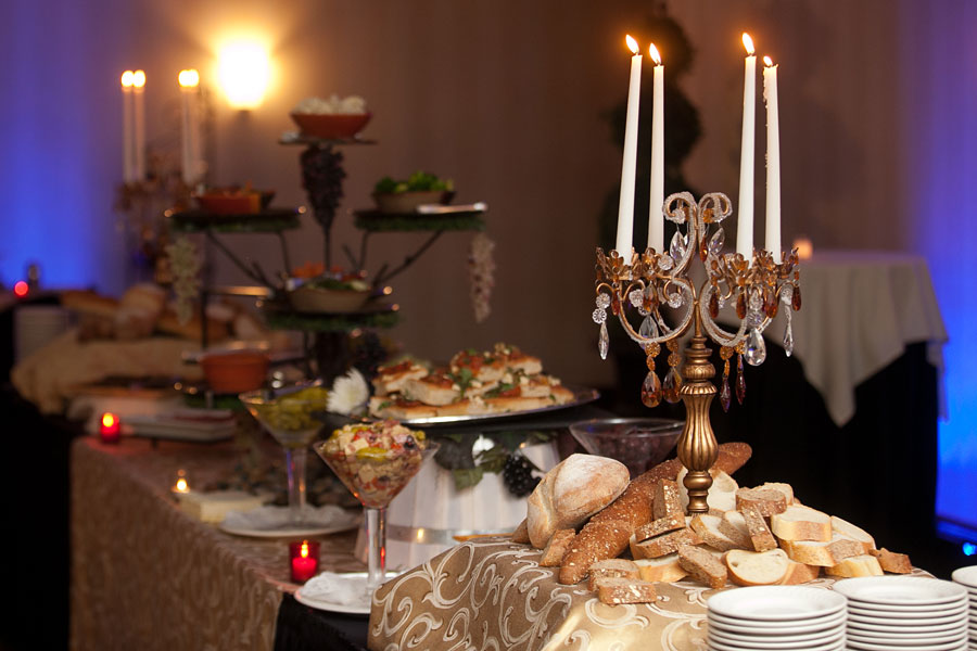 bread, appetizers and assorted dips on a table with a candelabra and four candles