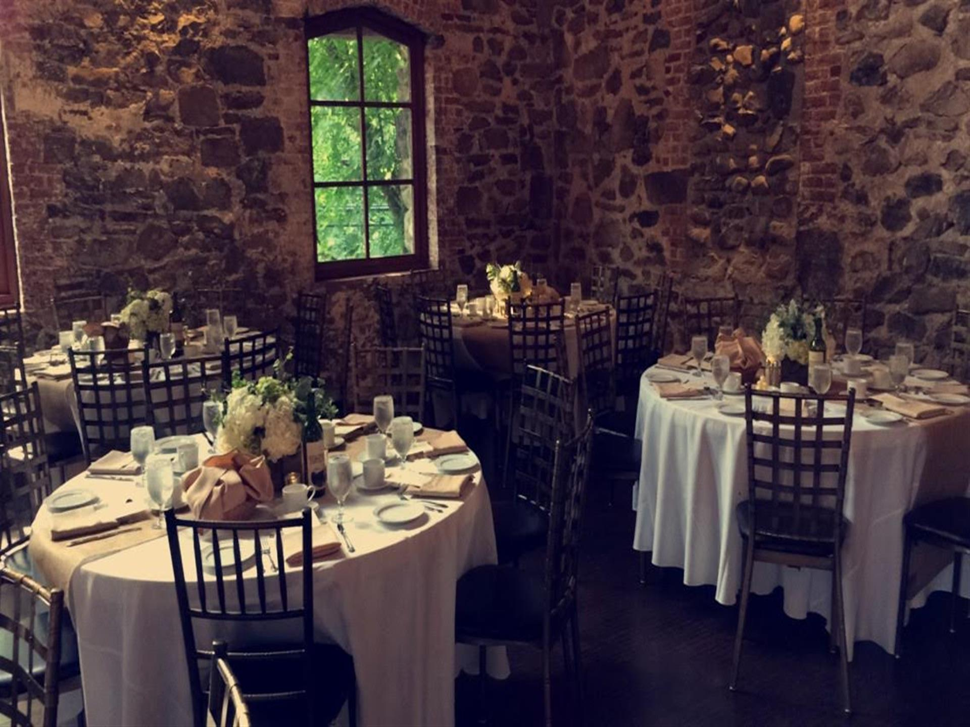 banquet tables set inside stone walled room