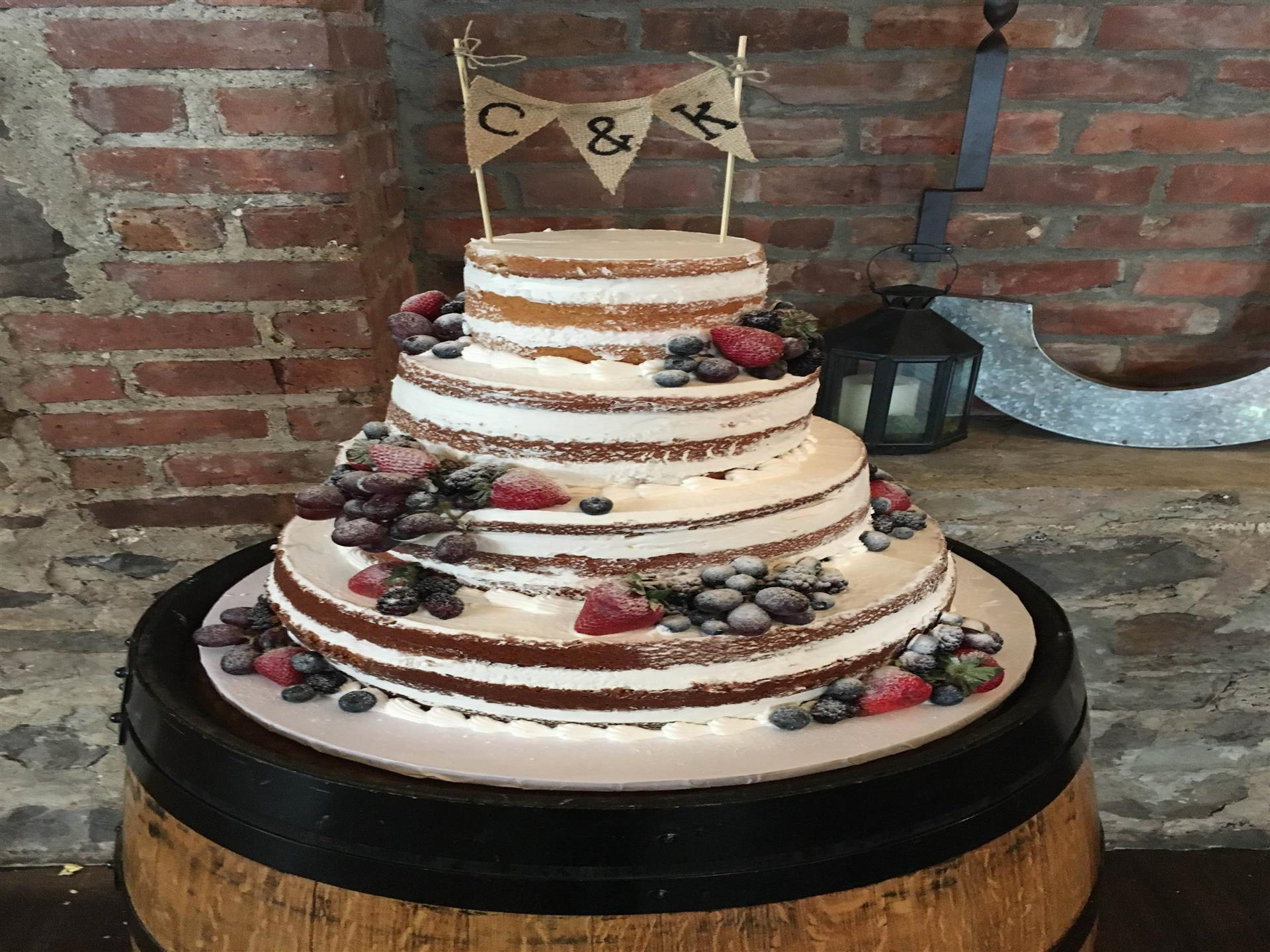 naked cake topped with strawberries and blueberries
