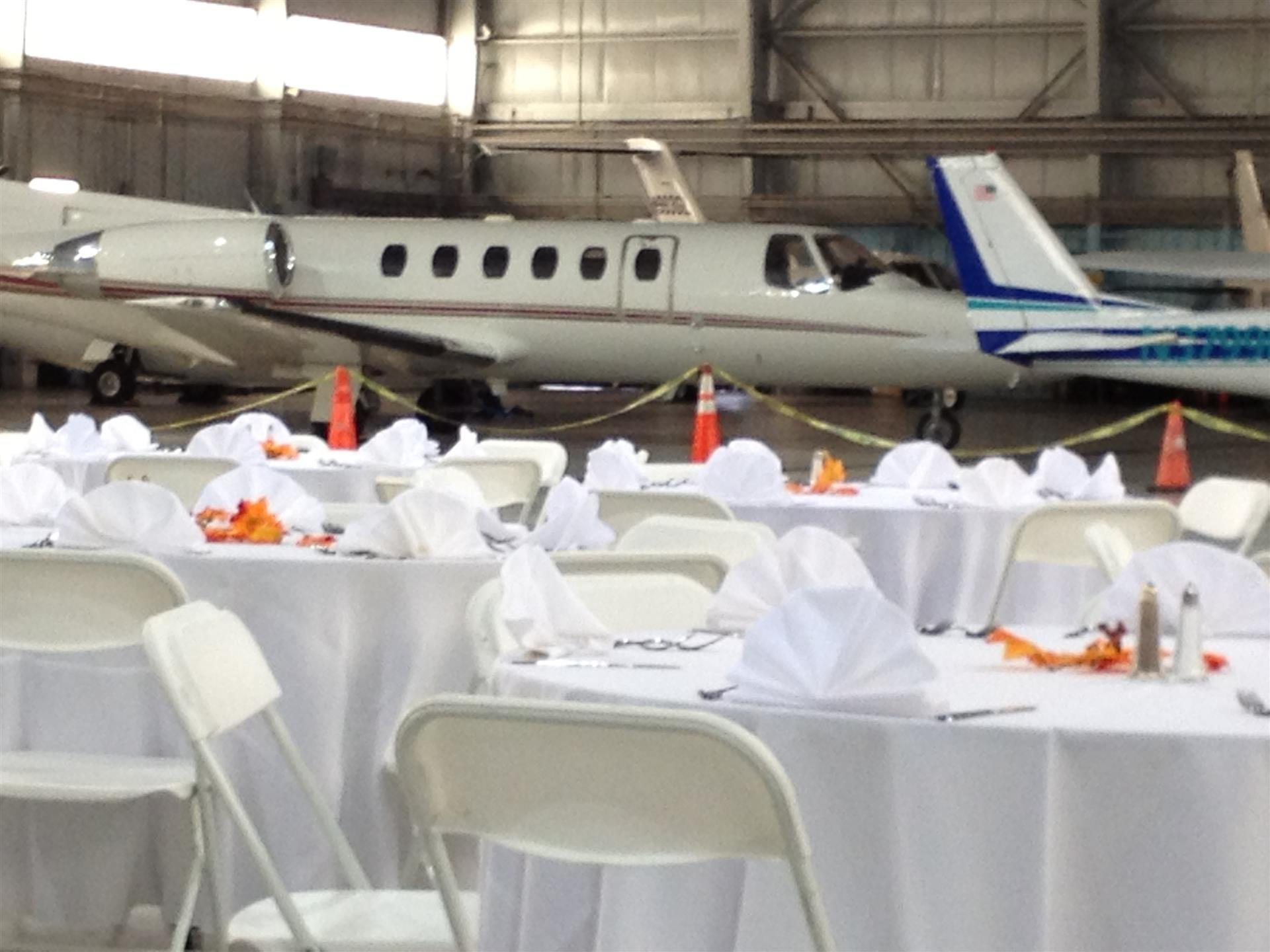 banquet tables set in an airplane hander with airplane in the background
