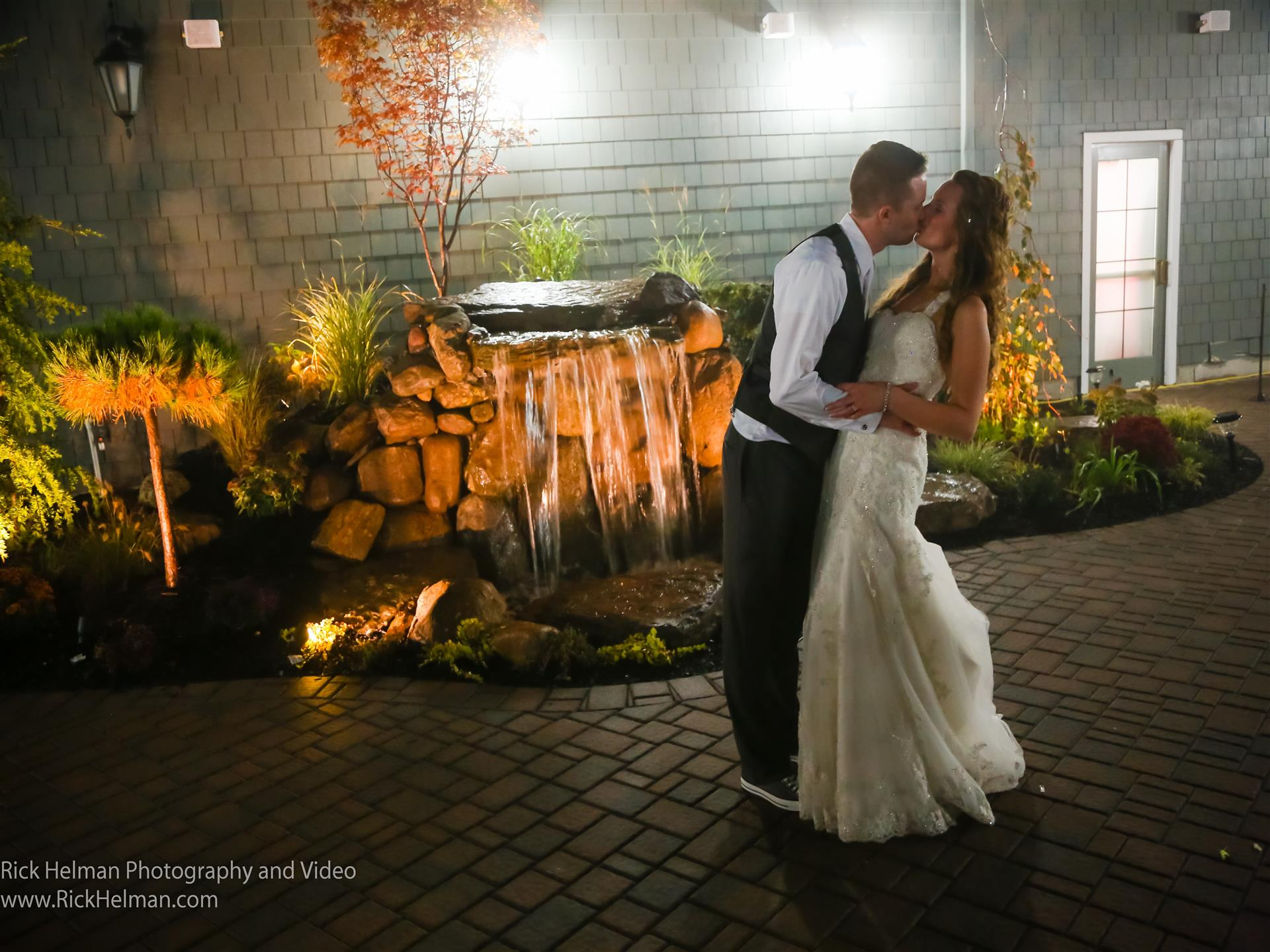 bride and groom kissing infront of waterfall