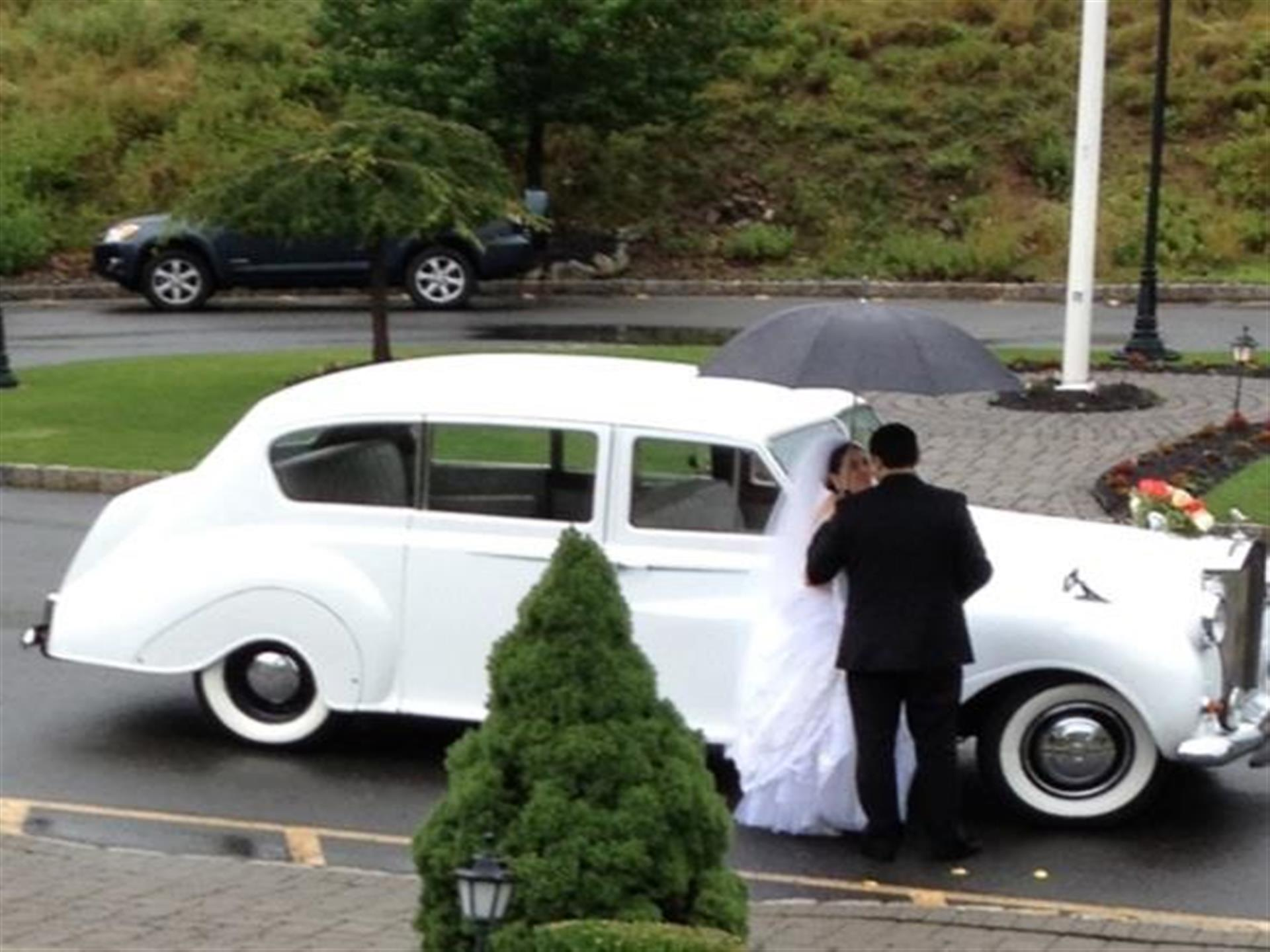 bride and groom kissing in front of a white car