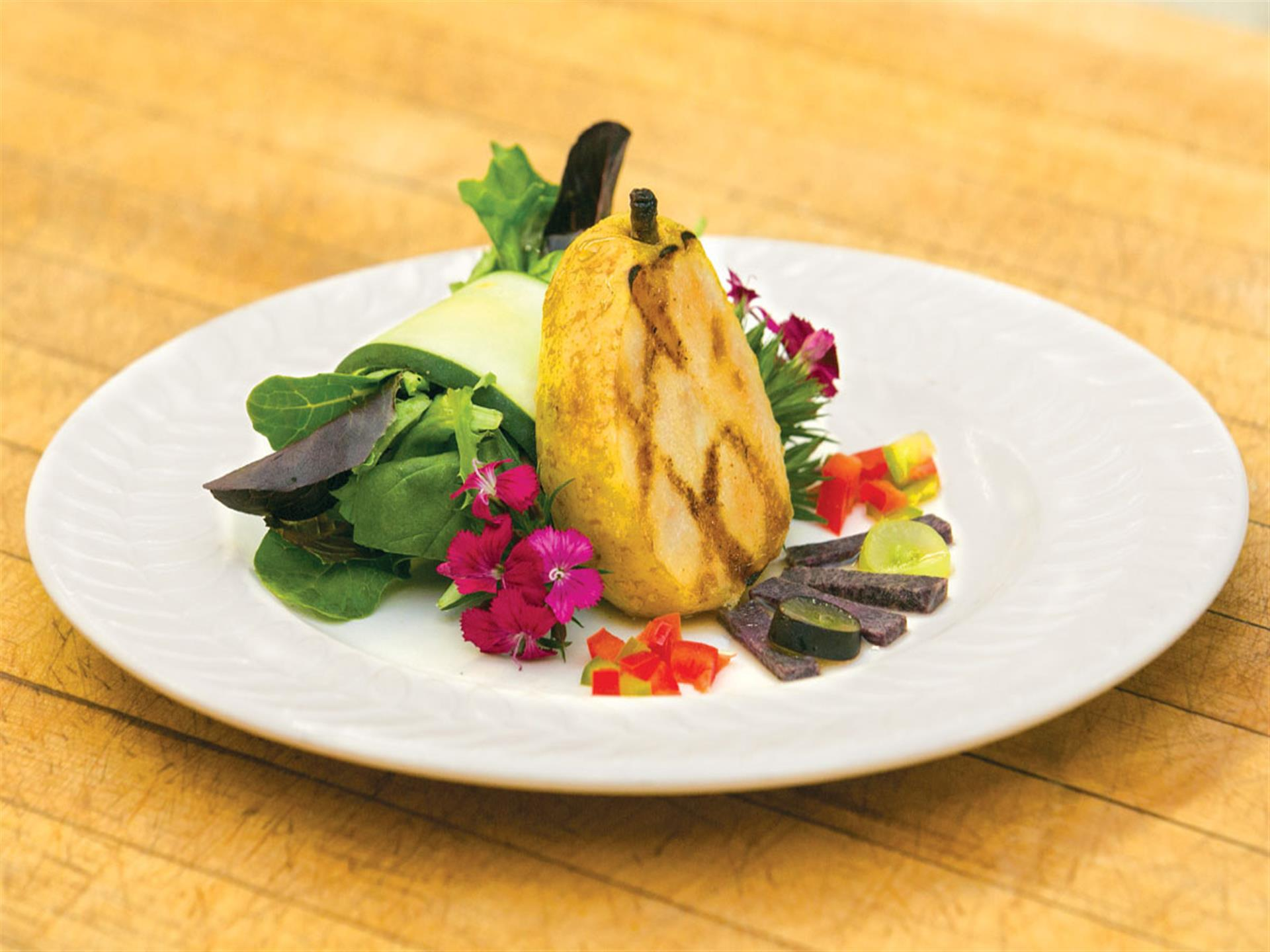 grilled pear dessert on a plate with edible flowers