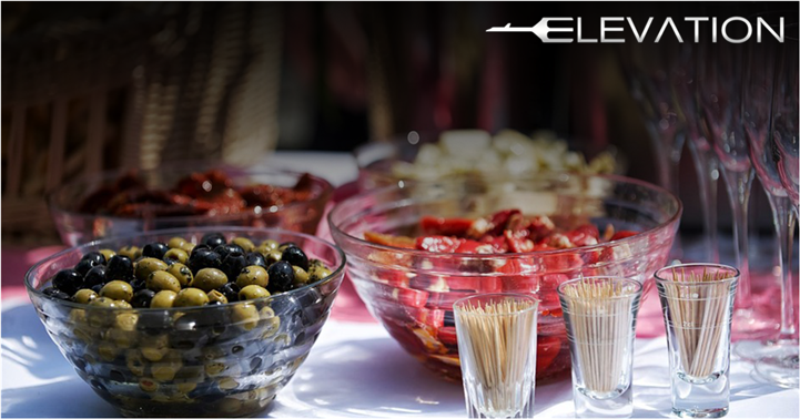 catering display table with a bowl of olives and a bowl of cooked peppers with a side of tooth picks