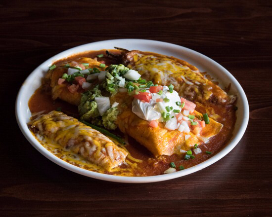 plate of enchiladas topped with sauce, melted cheese, sour cream, guacamole, pico de gallo, and scallions