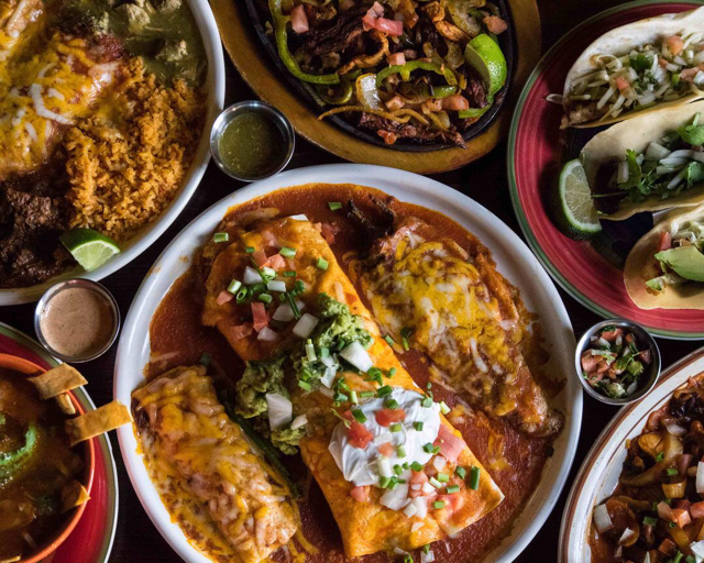 platters of enchiladas, carne asada, and beef and chicken fajita skillet