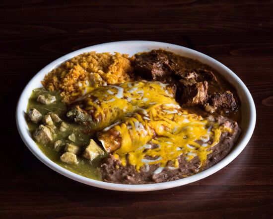 enchiladas topped with salsa verde, melted cheese, sides of rice and refried beans