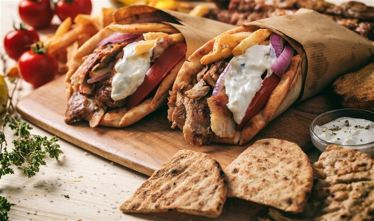 greek gyros on a wooden board with sliced pitas on the side